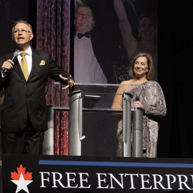 Greg and Laurie Duncan Giving a Speech on Stage