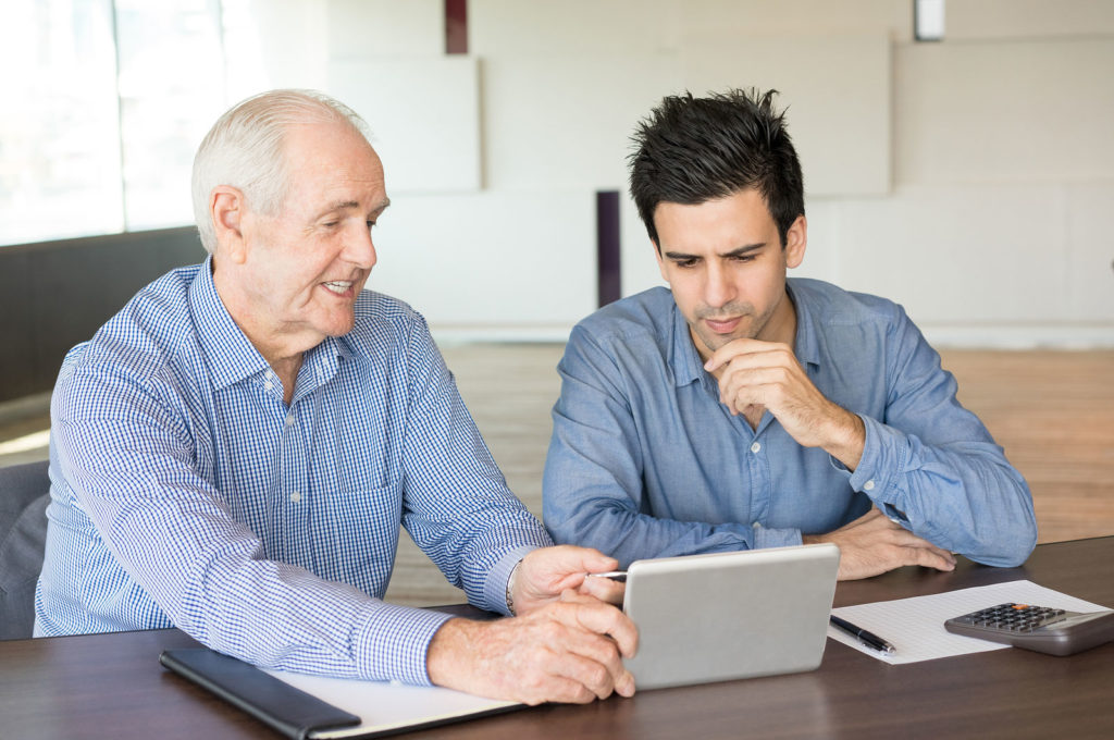 Older man and younger man working on a computer together